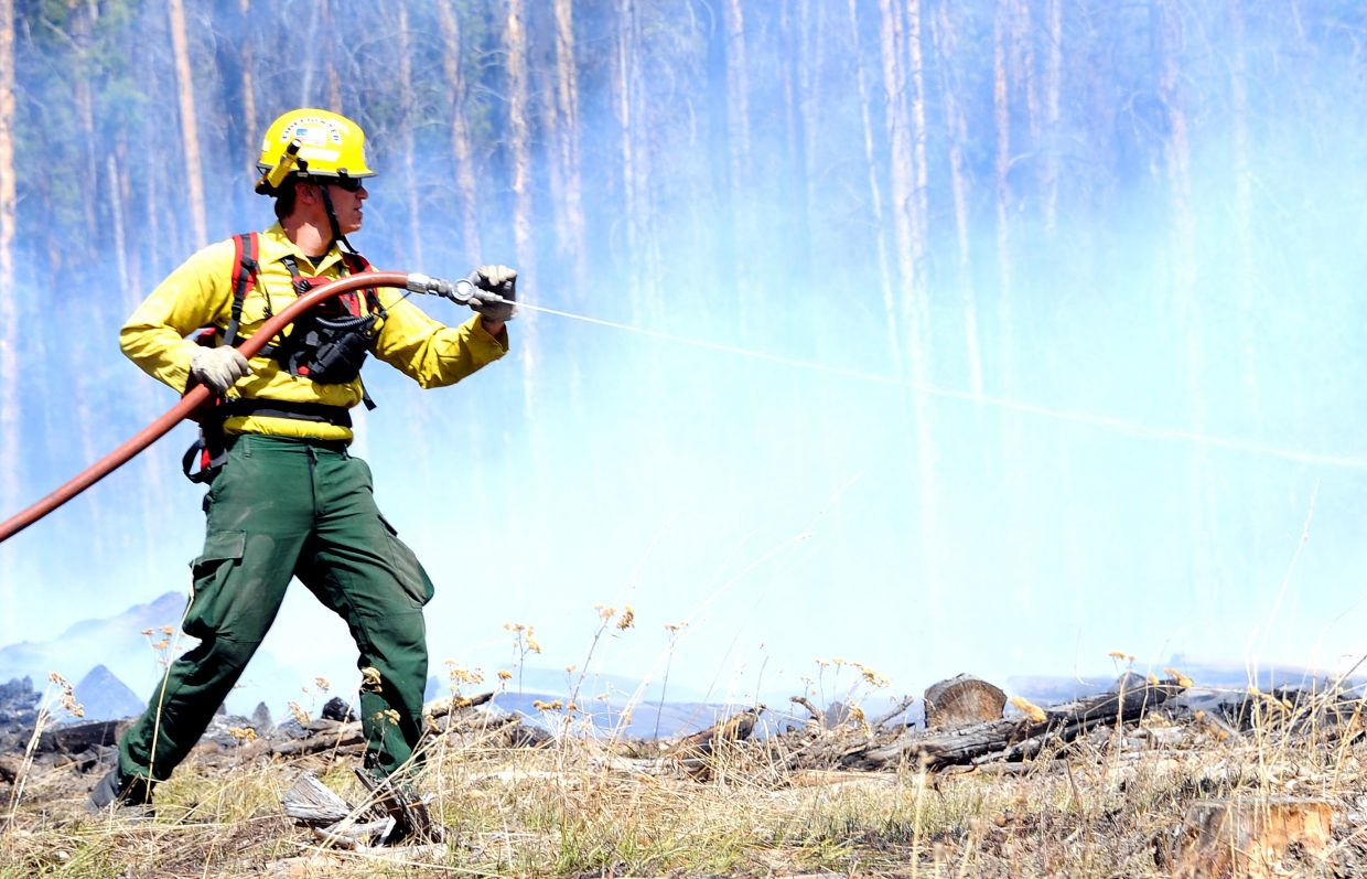 Oak Creek firefighter Kriss Bergethon blasts water into a smoldering area Friday while fighting fire in south Routt County.