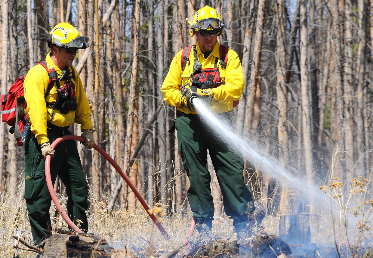 A fierce wind Friday takes controls of the water as Oak Creek firefighter Clinton Duncan soaks an area after a downed power line sparked a wild fire in south Routt County.