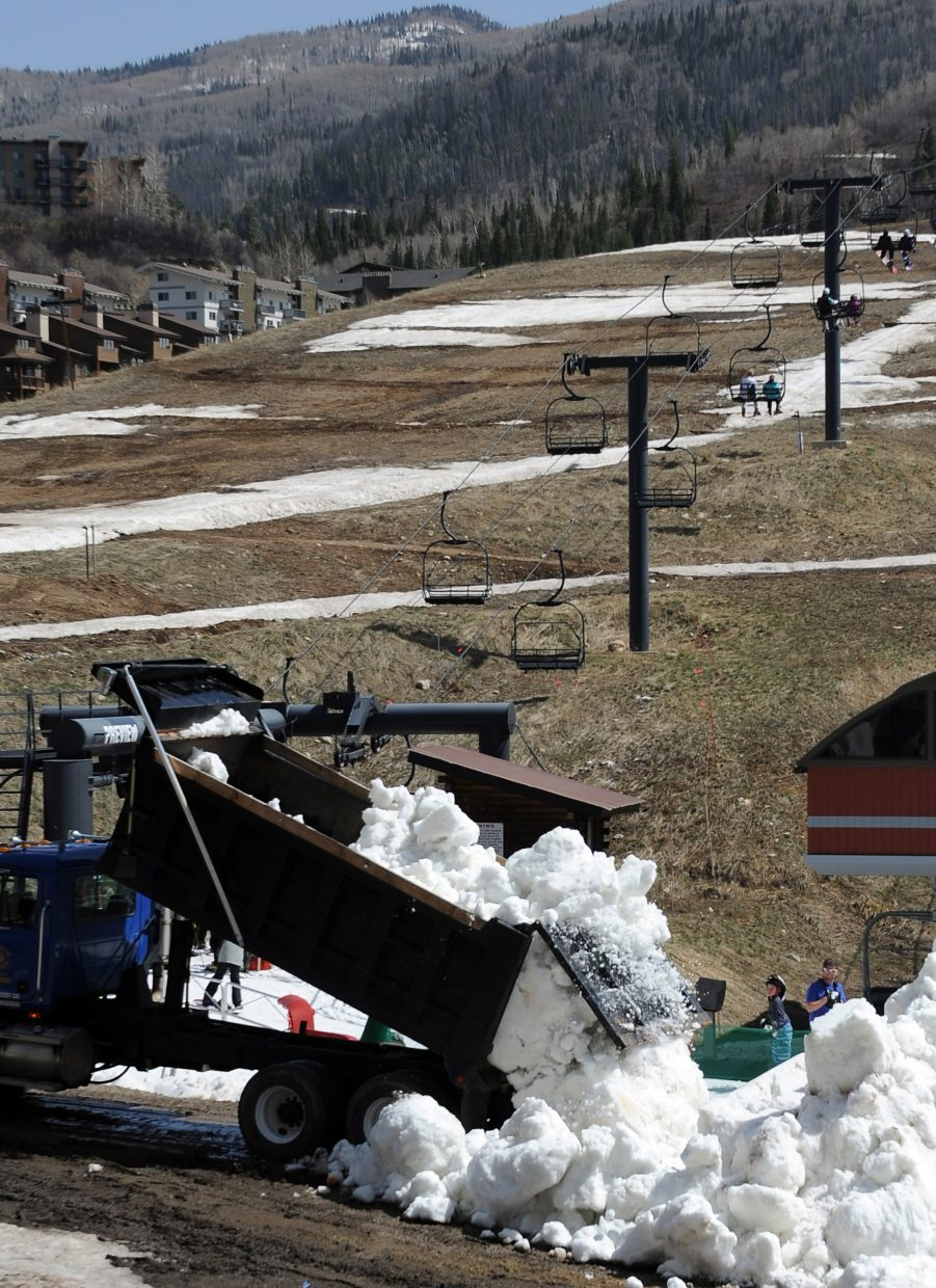 A dump truck unloads snow Friday at the base of Steamboat Ski Area as visitors to the resort ride Preview chairlift, the day's only available lift. High winds closed the gondola, but that was only a part of the ski area's problems. The resort spent the day trucking in snow from downtown stashes, hoping to pile enough to keep the lifts running through the planned April 15 closing day.