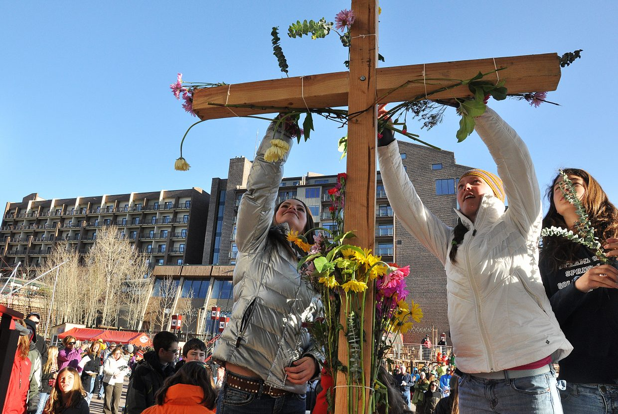 Nikki Katthain, left, and Jenna Miller place flowers on a cross Sunday morning during a sunrise Easter Mass in Gondola Square. Hundreds gathered for the Mass led by United Methodist Church of Steamboat Springs Pastor Tim Selby.