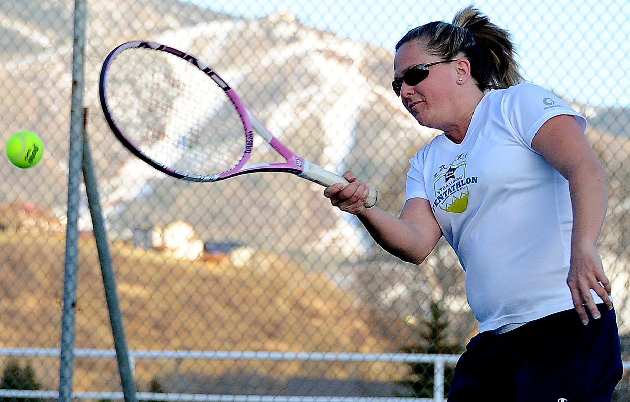 Jenica Walker swings for the ball while playing tennis Sunday evening at Howelsen Hill. She said there was a debate between her and her playing partner, Sean McCarthy, as to whether or not they should ski. She won, and they broke out the tennis equipment for the first time this season.