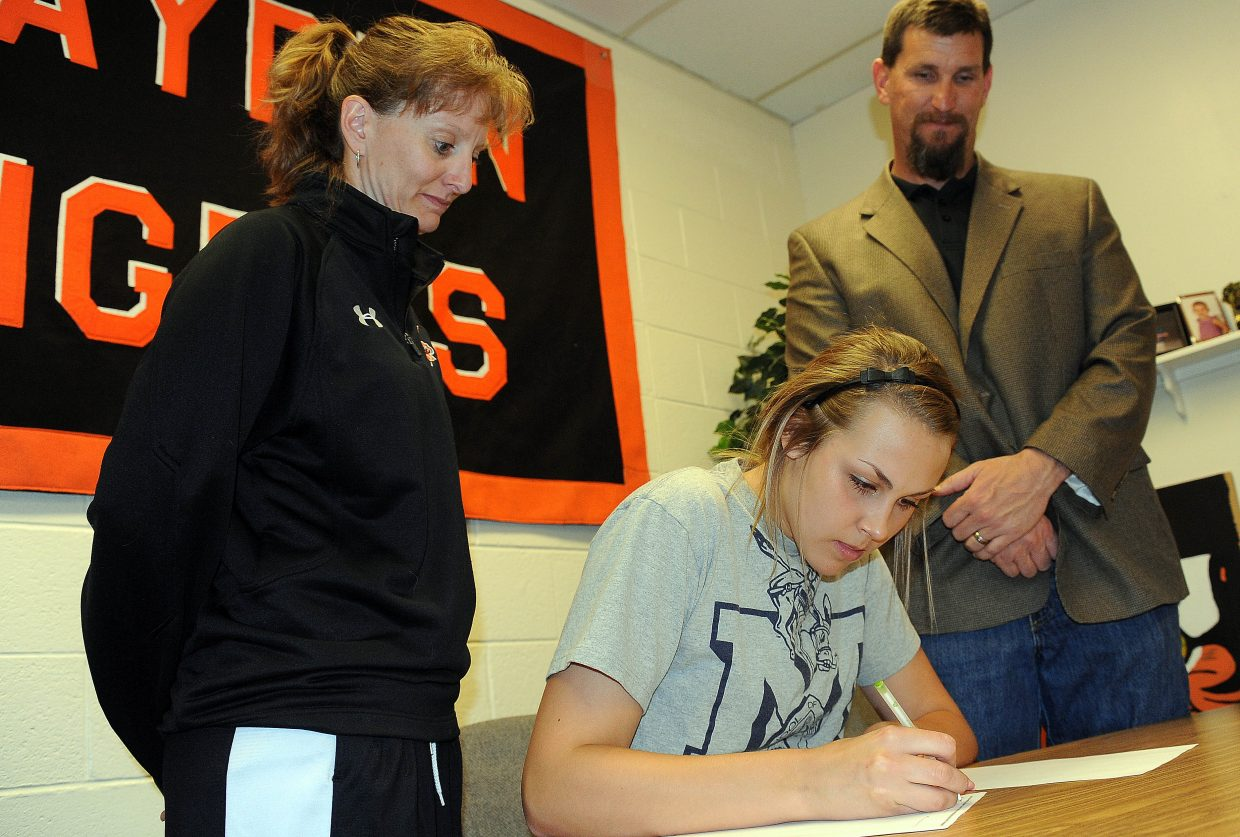 Hayden High School senior Erin Koehler, alongside girls basketball coach Michelle Wilkie and school athletics director Tony Rosso, signs a letter of intent to play basketball at Colorado School of Mines next season.