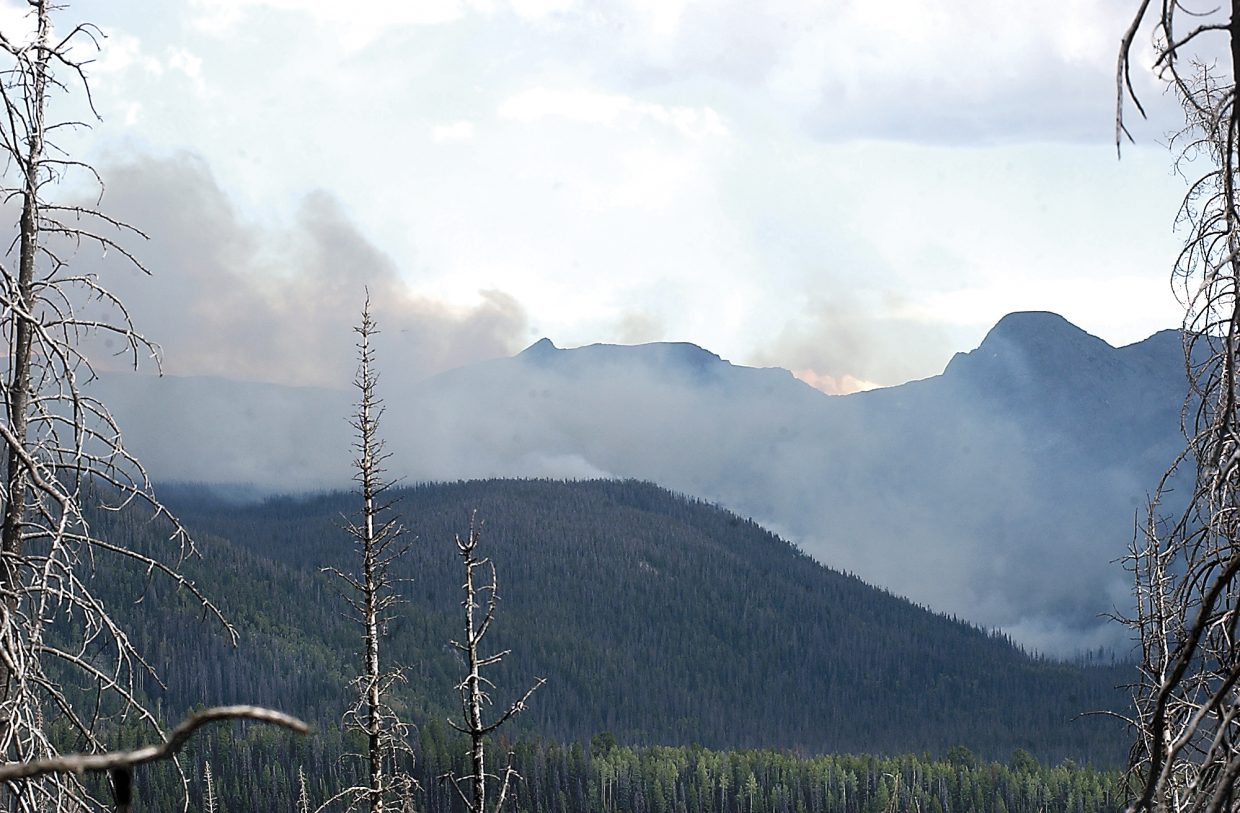 The Wolverine Fire burns a mountainside in the Routt National Forest in August 2005. In the foreground are the charred remnants of trees that fell victim to the Hinman Fire in 2002.