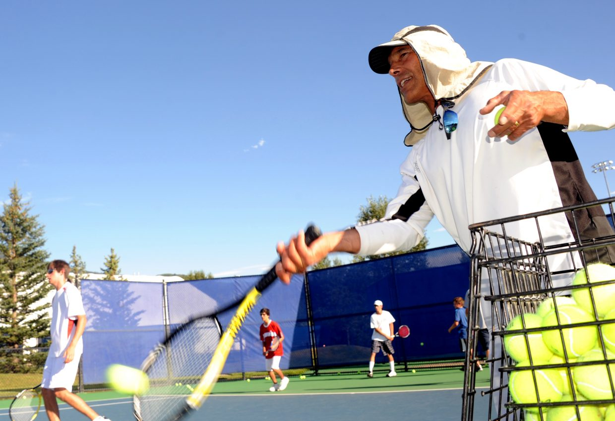 Steamboat Springs High School boys tennis coach John Aragon feeds balls onto the court during practice in August in Steamboat Springs. The boys tennis program is one of the Tier 2 sports that are in danger of losing funding because of a projected $30,000 athletics transportation deficit.