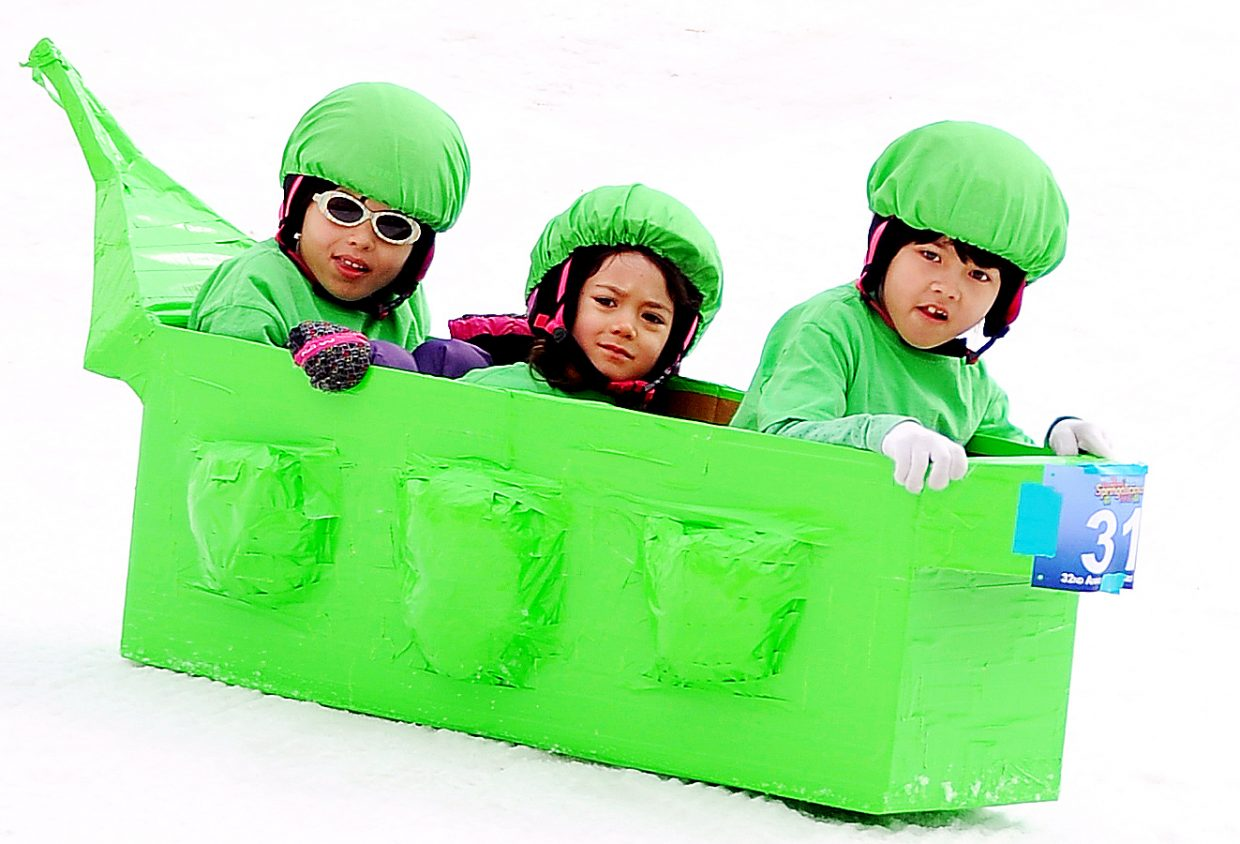 The Yamashita sisters — Julia, 9, left, Lilly, 5, and Madelyn, 7 — are three peas in their cardboard pod, skidding down the run at Saturday's Cardboard Classic event in Steamboat Springs.