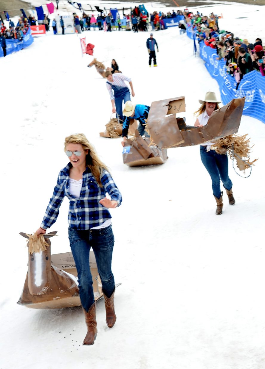 Cowgirls and cowboys stream down the slopes after their cardboard horses left something to be desired in the snow sliding category.