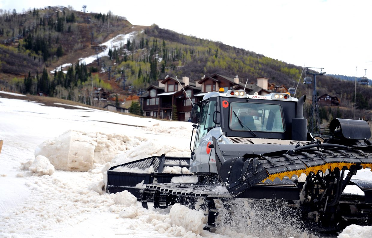 A snowcat pushes a pile of snow around the base area at Steamboat Ski Area on Friday. Pushing piles of snow isn't the most efficient way to handle it, but it was the only option this spring as a dry season and warm weather combined to test ski area slope maintenance crews. They managed to keep the mountain open to its planned Closing Day.
