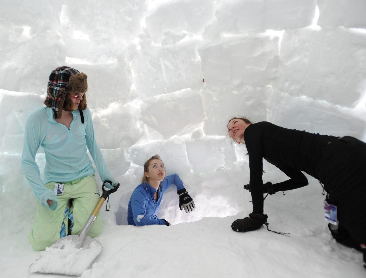 Meg O'Connell, left, Anala Sokolowski and Gabby Heron check out the inside of the igloo they built last weekend for an overnight camping trip on Rabbit Ears Pass. The hardest part, they said, was the digging, which O'Connell still was working on in an effort to smooth out the spot where their sleeping bags would end up.