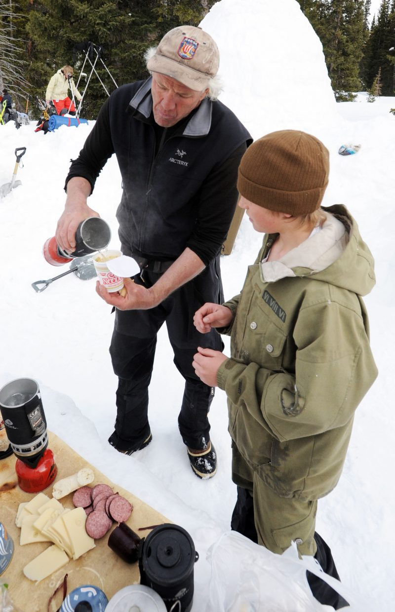EOS volunteer Pete Perry fills up Joe DeLine's cup of noodles with boiling water last weekend during an EOS camping trip on Rabbit Ears Pass.