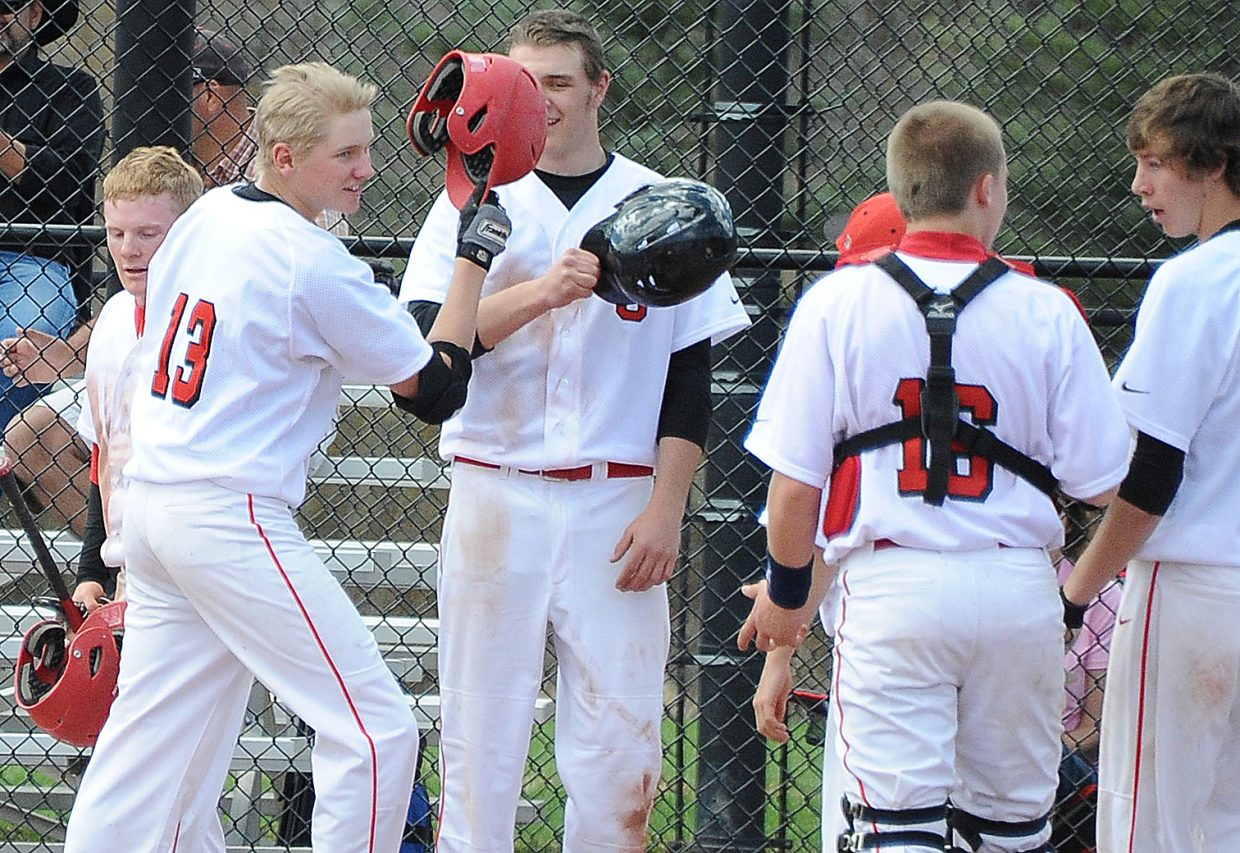 Steamboat's Thomas Kelly accepts congratulations from his teammates after bashing a three-run home run during the first game of Saturday's high school double header in Steamboat.