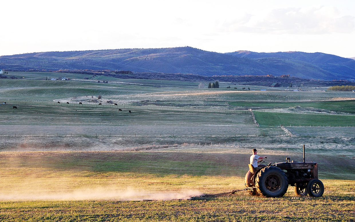 Bruce Brown harrows a field at sunset Sunday on a ranch south of Steamboat Springs.