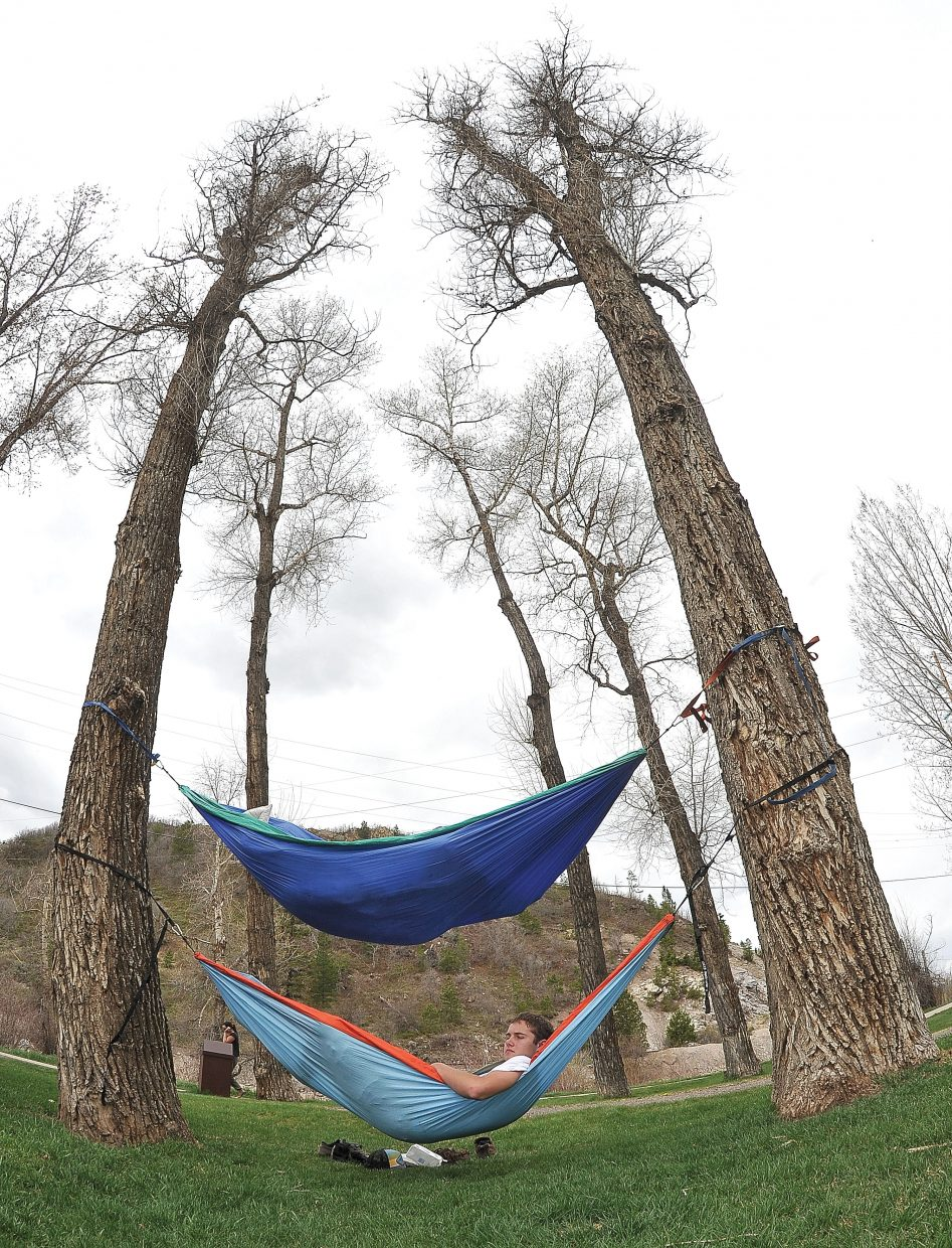 Colorado Mountain College student Michael Burns peeks out of his hammock Thursday afternoon while relaxing in Little Toots Park with his classmate Jared Wooden.
