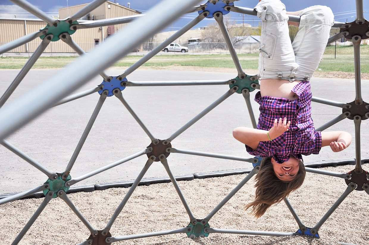 Shelby Archuleta hangs upside down on a play structure Tuesday during recess at Hayden Valley Elementary School. Although Shelby, a fifth-grader, will move into middle school next year, she said she's glad her younger classmates will be able to enjoy new playground equipment.