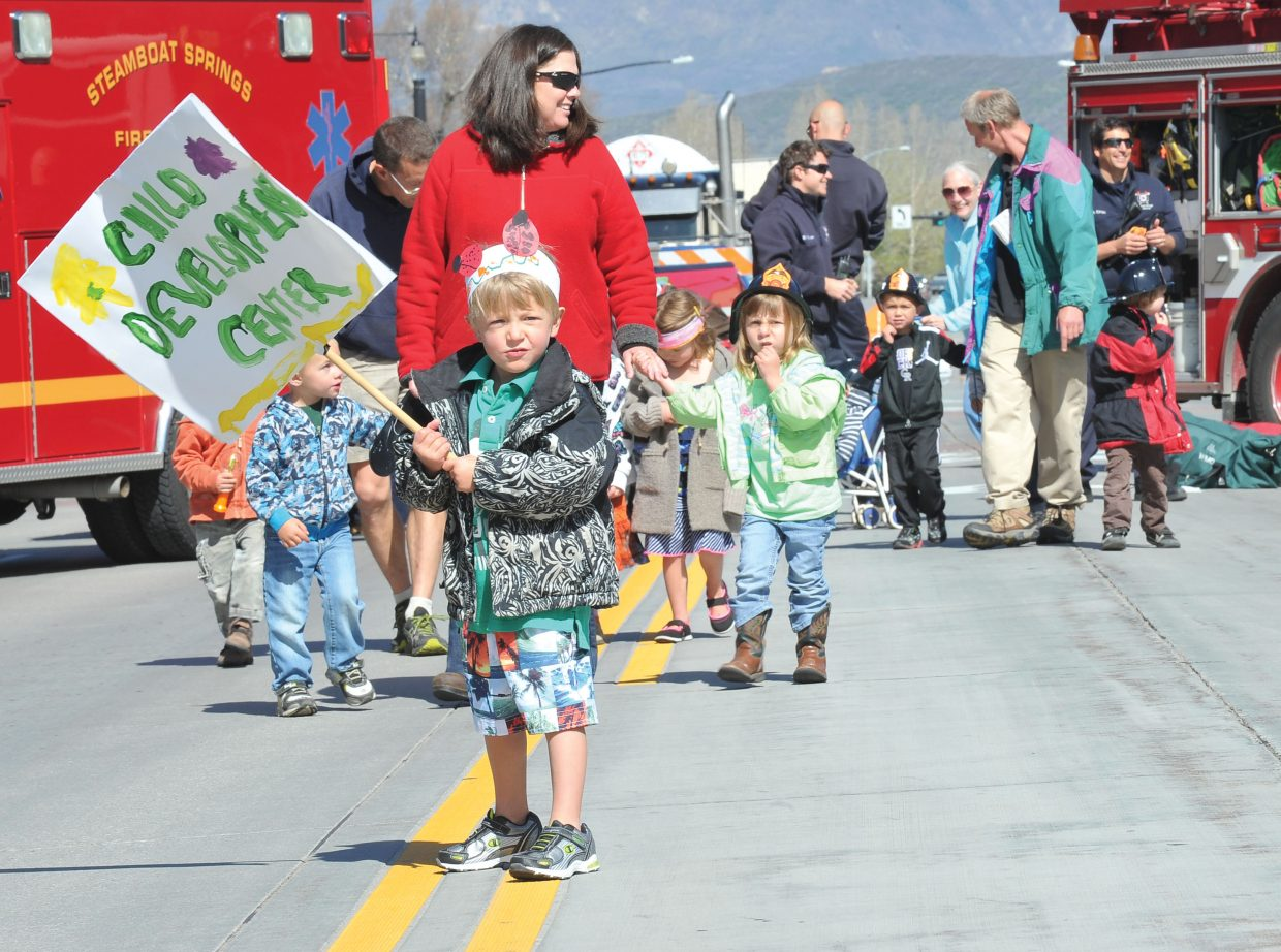Drew Picking holds a sign for the Child Development Center during Monday's Children's Parade on Lincoln Avenue. The annual parade is part of the Month of the Young Child celebration.