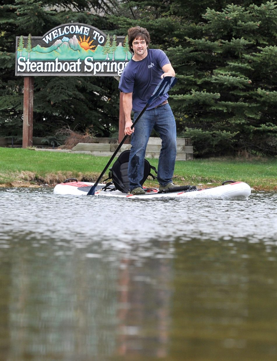 Peter Hall cruises across the lake in West Lincoln Park on his inflatable paddle board Tuesday afternoon.