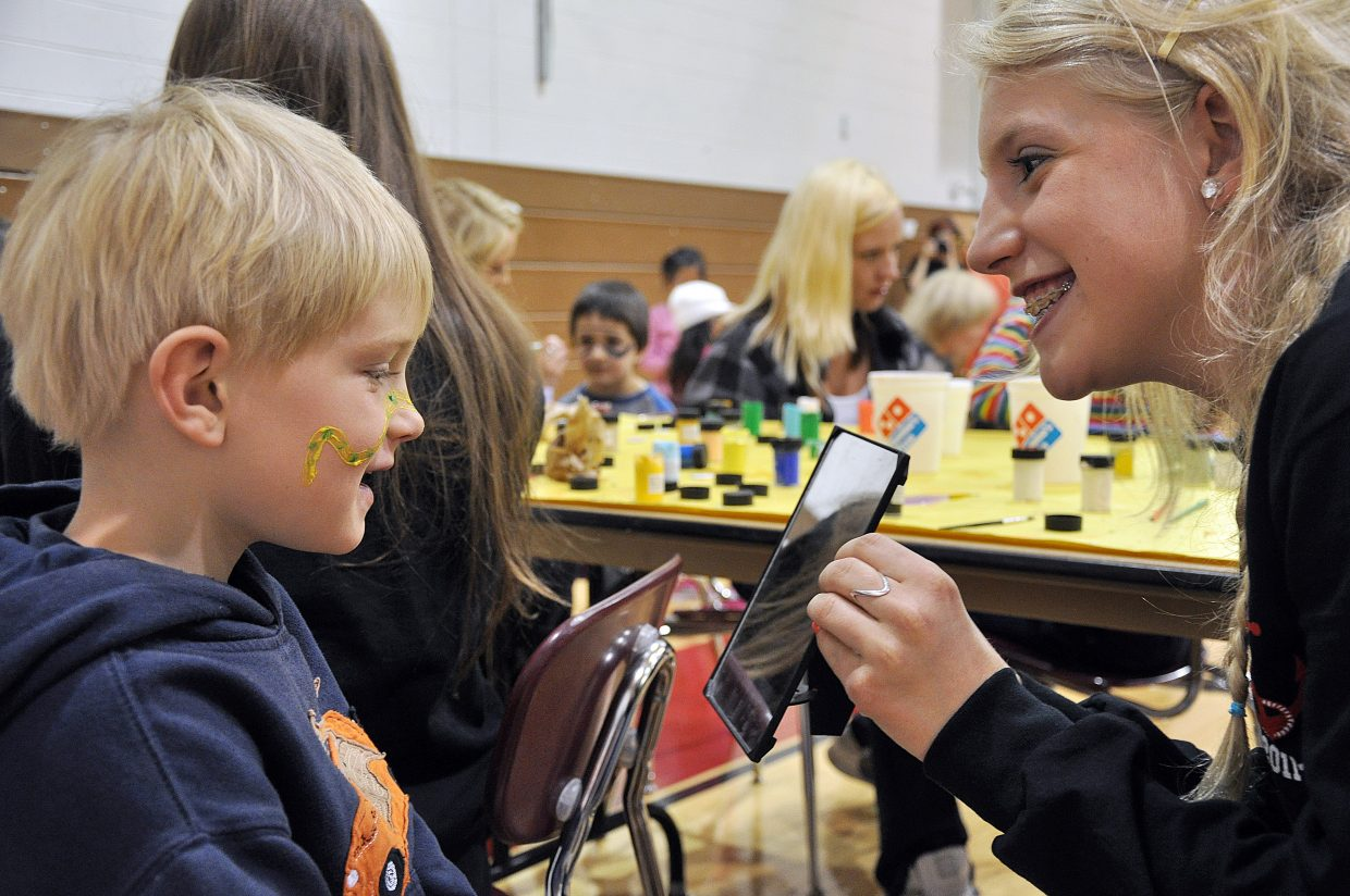 Connor Frithsen, of Strawberry Park Elementary School, admires the snake painted on his face Wednesday by Steamboat Springs High School sophomore Malia Fraioli.