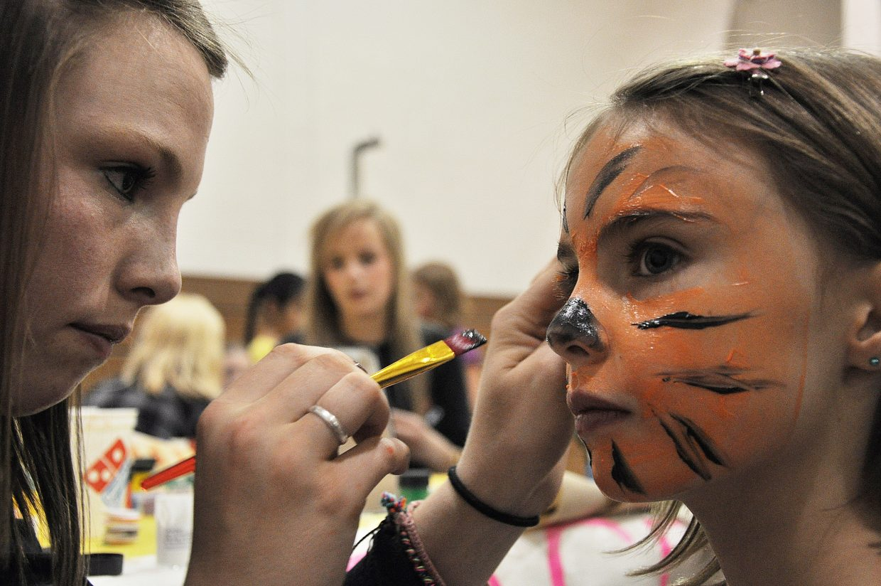 Amaris Duryea paints Isabella Brinkman's face like a tiger Wednesday during Steamboat Springs High School's Kids Carnival. Preschoolers through second-graders enjoyed games and events at the carnival that filled the high school's gymnasium.