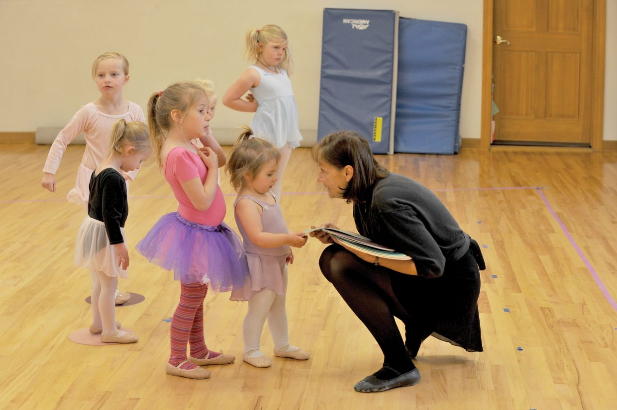 Dance instructor Tamara Bereznak hands out mats to her students while rehearing at the Let's Dance studio in Oak Creek Wednesday.