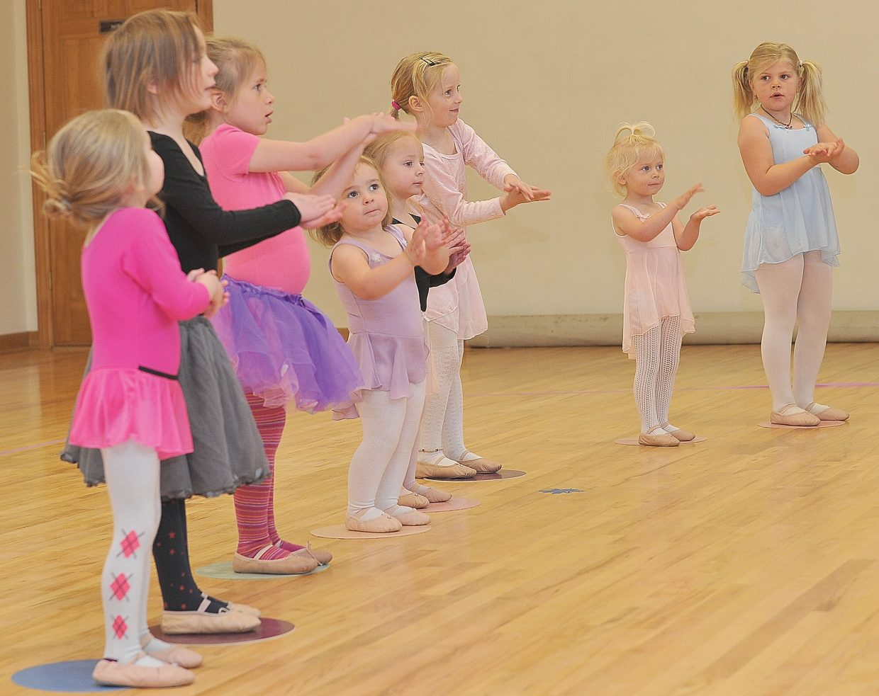 Clara Bruski (middle in purple) warms up with her classmates at the Let's Dance studio in Oak Creek Wednesday morning.