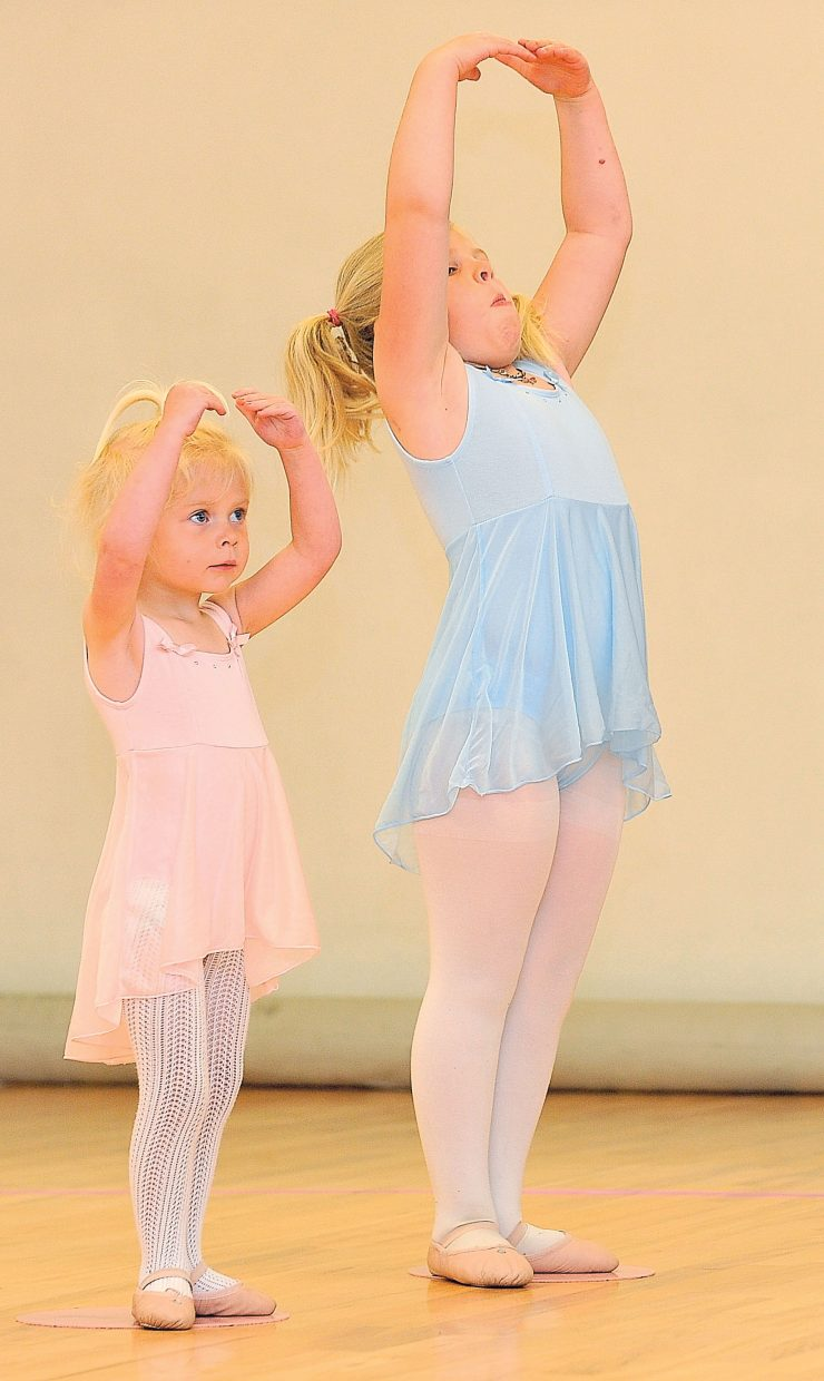 Young dancers Caroline and Madeleine Erps work on their moves during a lesson at the Let's Dance studio in Oak Creek Wednesday.