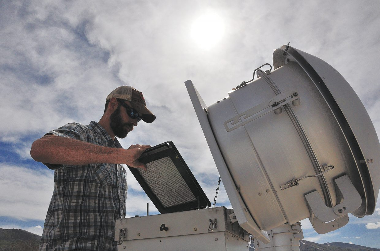 Routt County Environmental Health specialist Jason Striker changes out the filter of an air quality monitor Thursday on top of the Routt County Courthouse in downtown Steamboat Springs. County commissioners are planning to add sensors on the roof and in western Routt County capable of detecting oil and gas emissions.