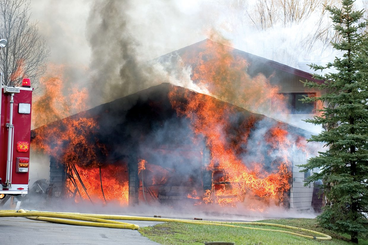 Flames engulf a garage on Deerfoot Avenue in downtown Steamboat Springs on Wednesday morning. The fire was contained to the garage and the occupants and four dogs were able to escape without injury.