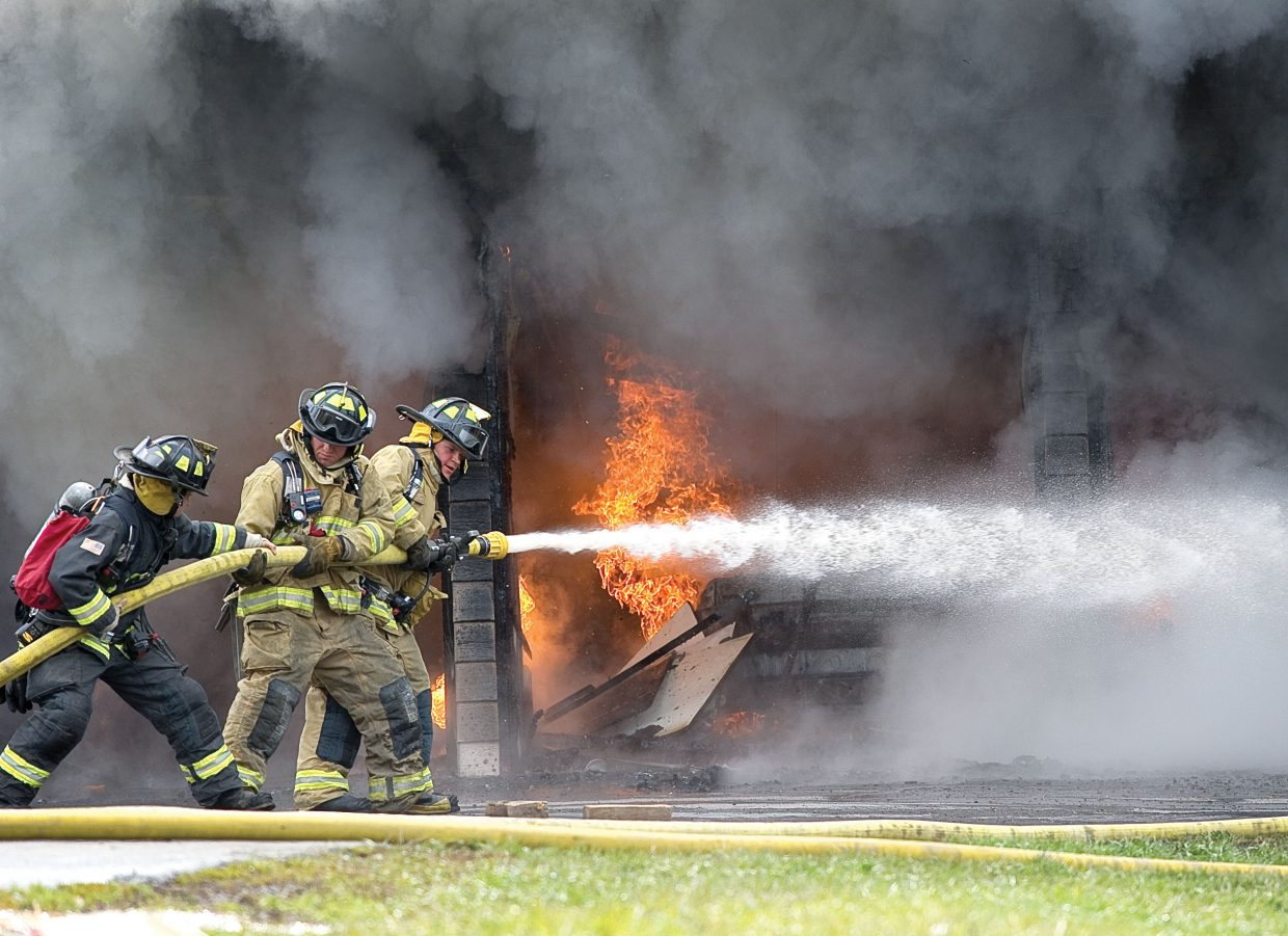 Members of Steamboat Springs Fire Rescue fight to get into position as they battle a blaze on Deerfoot Avenue on Wednesday morning. The blaze started in and was contained to the garage.