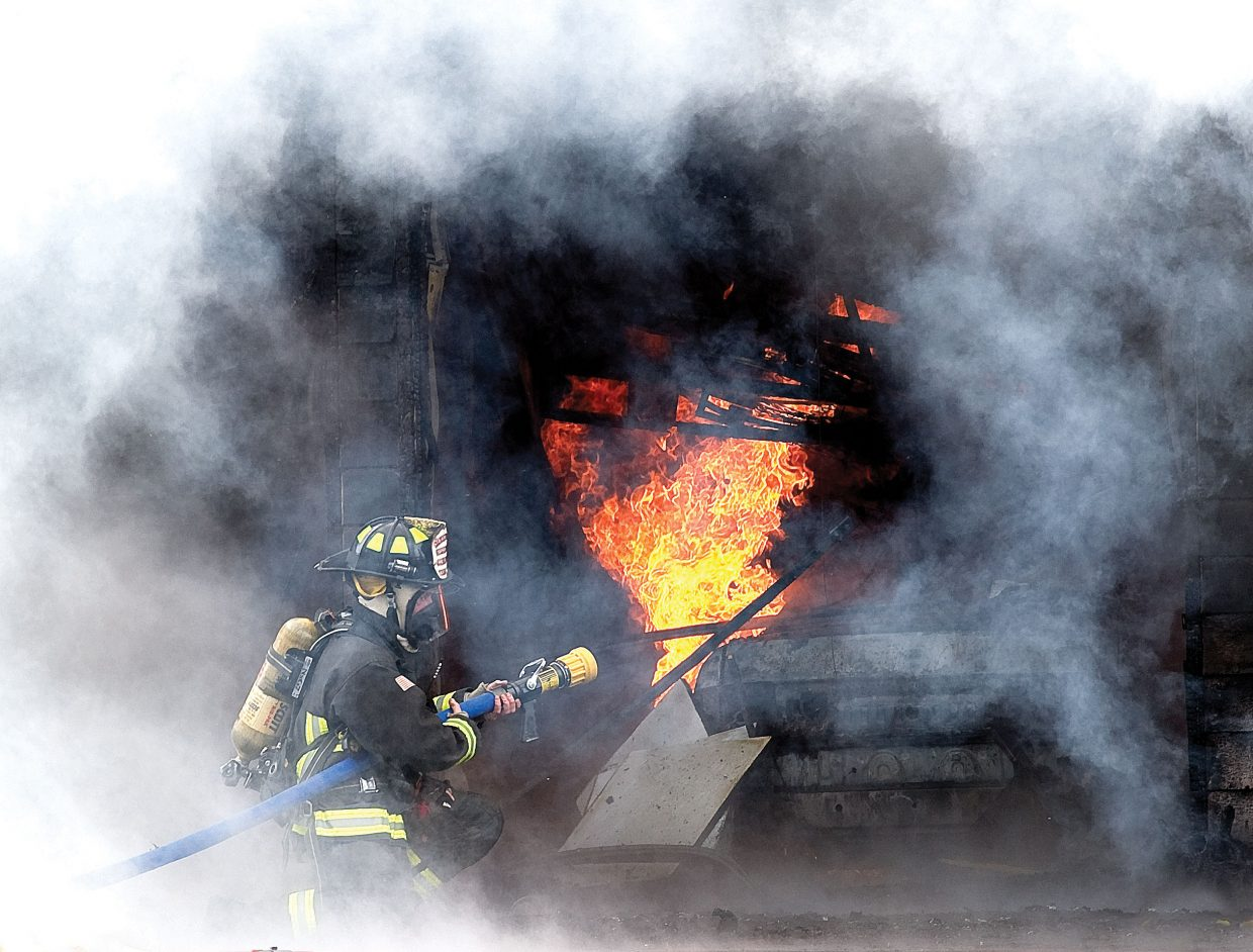 A Steamboat Springs Fire Rescue firefighter aims a hose toward flames in a garage on Deerfoot Avenue on Wednesday morning. No one was injured in the fire.
