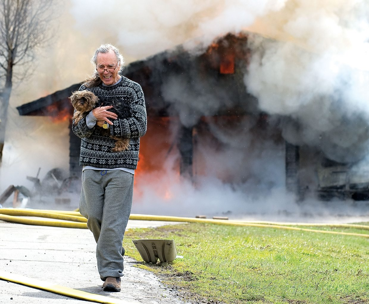 Chris Kipfer carries a dog away from his home on Deerfoot Avenue on Wednesday morning. Steamboat Springs Fire Rescue responded to a fire that apparently started in the garage of the home shortly before 11 a.m.