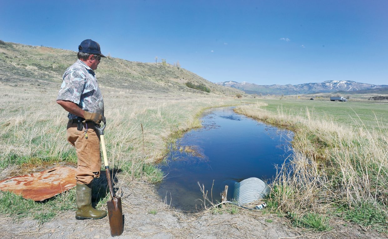 Local rancher Michael Hogue checks an irrigation ditch on his property west of Steamboat Springs. Conditions are good right now, but the nearly bare slopes of Steamboat Ski Area, shown in the background, could signal a dry summer across the valley.