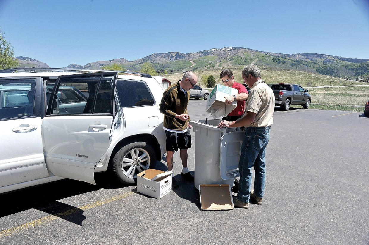 Steamboat Springs resident Jay Weinberg gets a helping hand from Alpine Bank employee Jeremy Behling, center, and John Radosevich, a security technician with Colorado Document Security, during Wednesday's Shred-A-Thon at Alpine Bank in Steamboat Springs. The bank in the past has hosted five shred-a-thons where local residents can bring outdated, sensitive documents containing personal information to be destroyed and is planning another in September.
