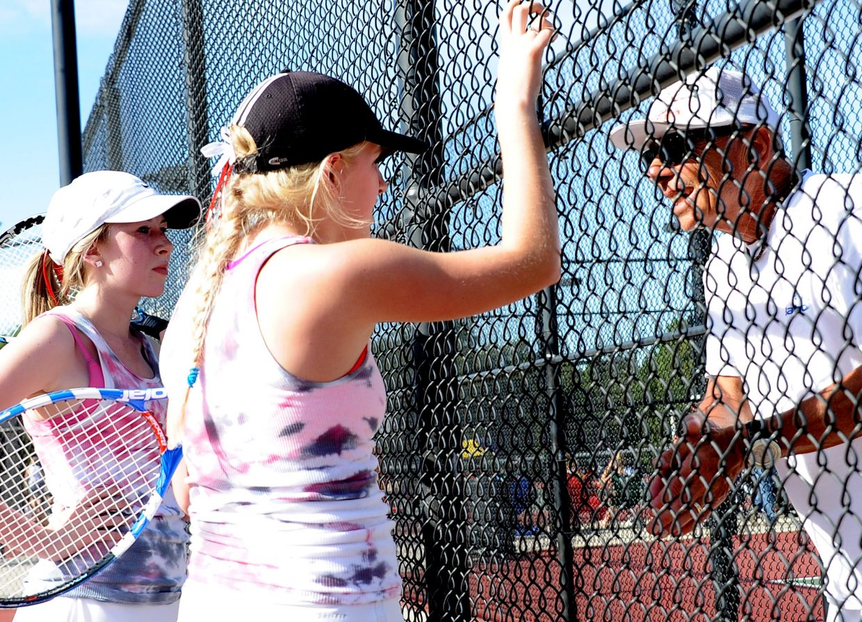 Steamboat coach Don Toy offers advice to the Sailors No. 4 doubles team Thursday.