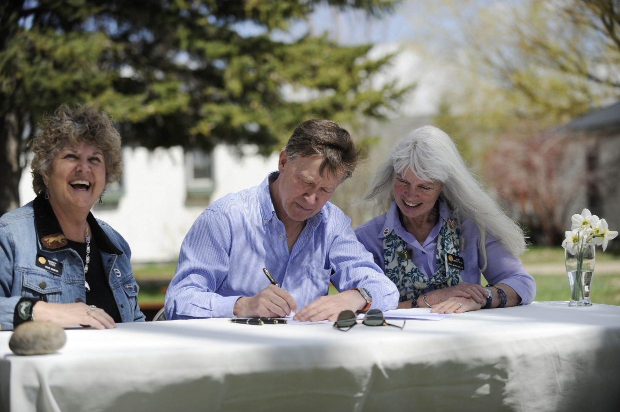 Sen. Nancy Todd, D-Aurora, left, and State Rep. Diane Mitsch Bush, D-Steamboat Springs, sit at a table with Colorado Gov. John Hickenlooper as he signs House Bill 1278 on Saturday at the Carpenter Ranch near Hayden.