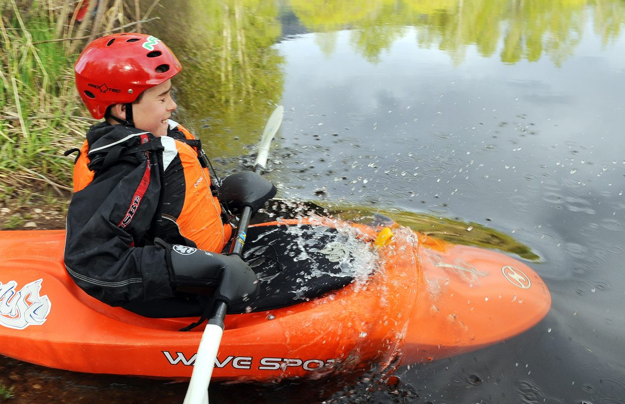 Spencer Schlegel, 11, splashes into the water Saturday. Spencer and his father, longtime kayaker Gary Schlegel, were taking a quick brush-up lesson with the Mountain Sports Kayak School's Barry Smith.
