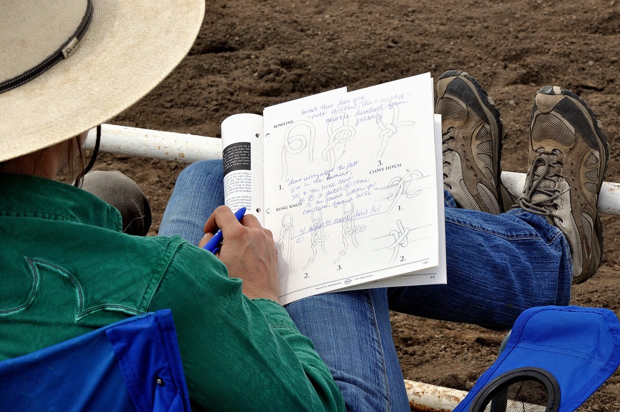Katie Nelson, of Evergreen, takes notes Sunday during the Buck Brannaman horsemanship clinic in Hayden.