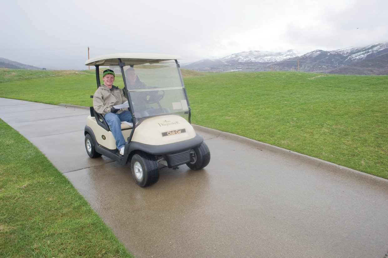 Steamboat Springs High School student Wesley Williams drives a cart along with classmate Tom Lyon while cleaning birdhouses at the Haymaker Golf Course earlier this week.