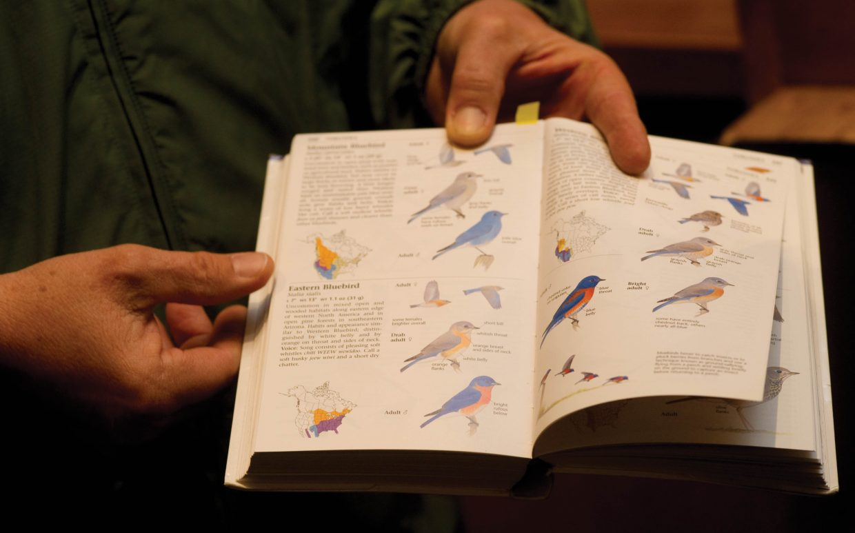 Local bird expert Tom Litteral, a member of the Yampa Valley Birding Club holds a book about birdes while talking to high school students at the Haymaker Golf Course on Wednesday.