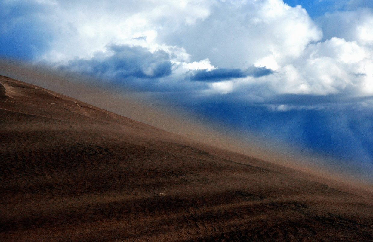 Wind from an approaching storm whips ups sand on the dunes.