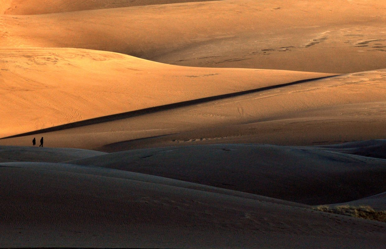 Two boys begin the hike up the sand dunes at sunrise. The dunes offer many opportunities to ski, sled and hike.