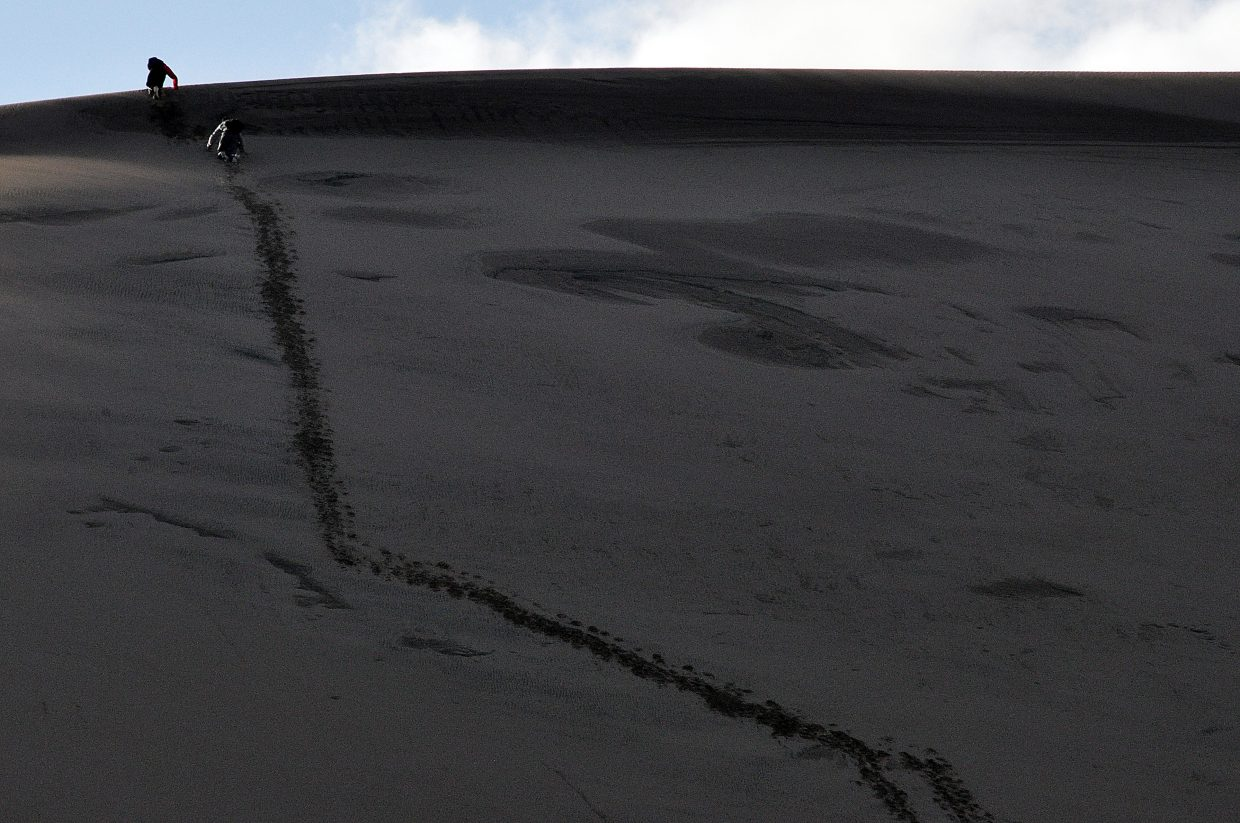 Two friends hike a steep dune to sled down it. Snowshoes and cross-country skis also can be used to traverse the dunes.