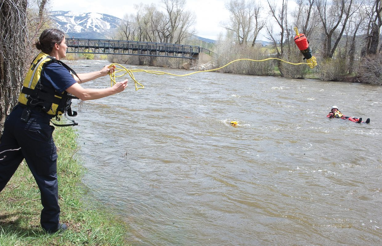 """Steamboat Springs Fire Rescue's Julie Wernig runs through a swift water training session with her fellow firefighters Thursday afternoon on the banks of the Yampa River. Water levels are very high with spring runoff, and water temperatures are very low, creating dangerous conditions. Steamboat Springs Fire Rescue Captain Travis Wilkinson warns residents to use extra caution around fast-moving streams and rivers this time of year and to always wear a life jacket in wildwater ways like the Yampa. """"It's easy to be complacent around the Yampa because there is so much recreation on the river, but in the springtime, the high water can be very dangerous,"""" Wilkinson said. He recommends that recreational users wait until water levels drop to get into the river and that users such as kayakers make sure they have a life jacket and practice river safety."""
