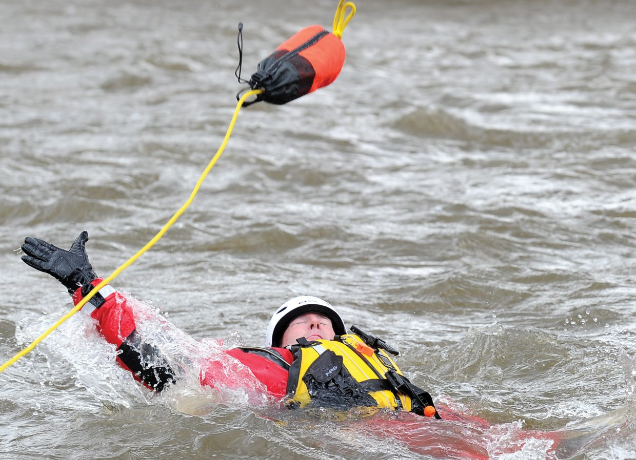 Steamboat Springs Fire Rescue's Matt Workman reaches for a rope bag during a swift water training session with fellow firefighters Thursday afternoon in the Yampa River.