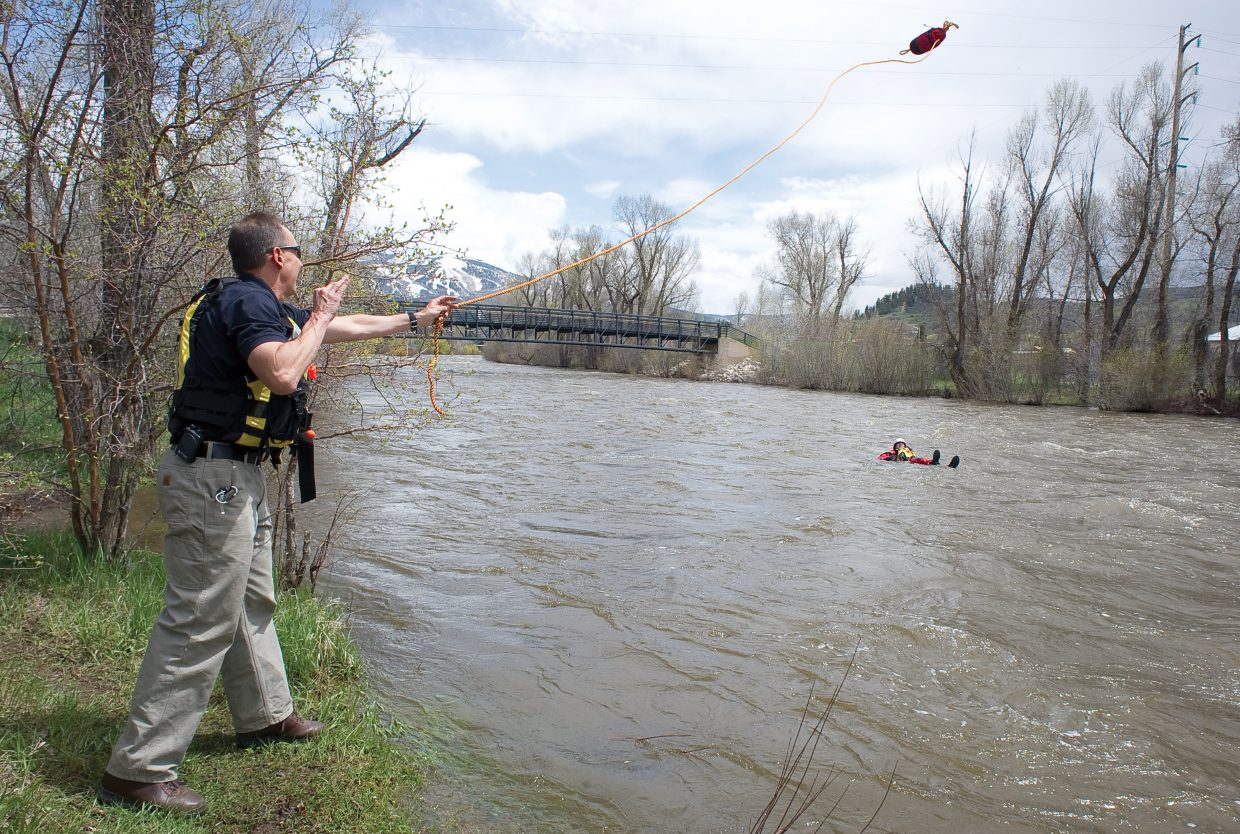 Steamboat Springs Fire Rescue Chief Mel Stewart throws a rope bag to a fellow firefighter while completing swift water training Thursday on the Yampa River.