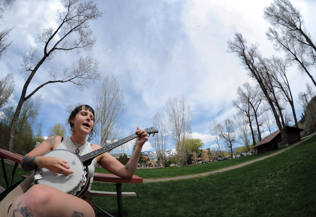 Pepper Pearl takes advantage of the warm weather Friday afternoon to play her banjo in the park.
