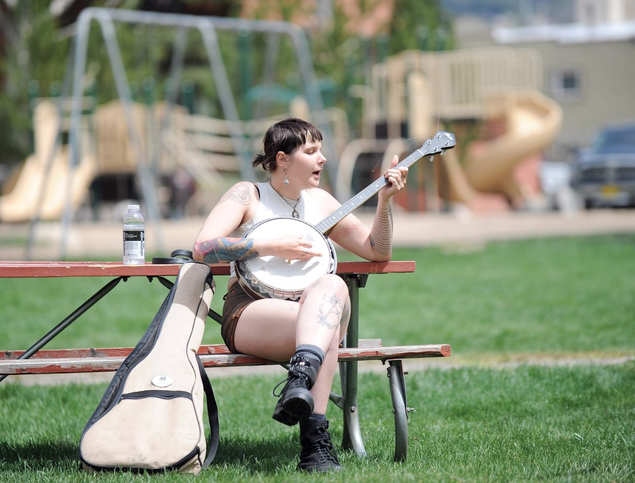 Pepper Pearl took advantage of the warm weather Friday afternoon to play her banjo in the park.