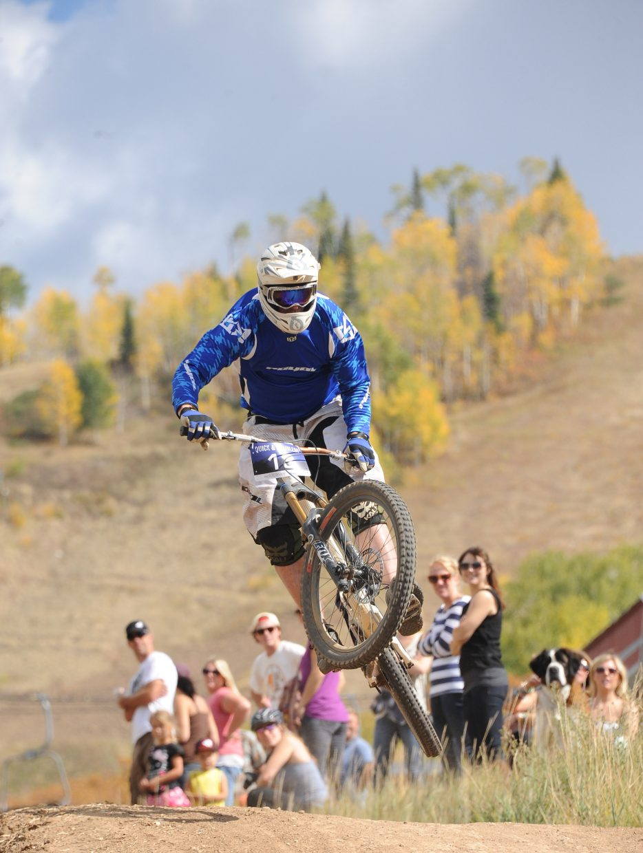 Adam Smith flies over a jump as the crowd cheers during the 2012 Quick and Chainless Downhill Mountain Bike Race at Steamboat Ski Area.