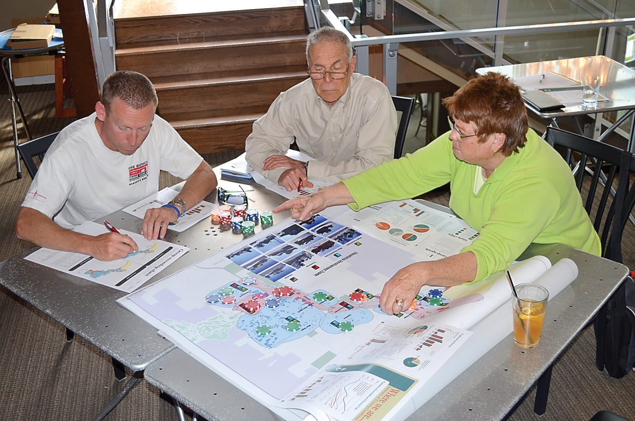 Mike Lang, from left, Bill Moser and Tracy Barnett use poker chips to plot the future development of Steamboat and its immediate surroundings this week. They were participating in an exercise hosted by city and county planners who are working on an update of the Steamboat Springs Area Community Plan.