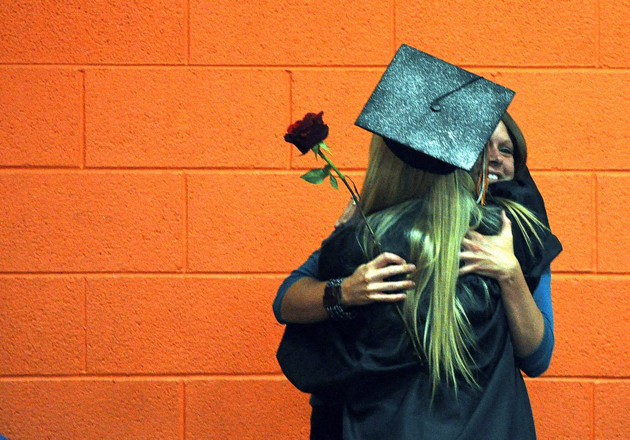 A graduate gets a hug Sunday following the ceremony at Hayden High School.