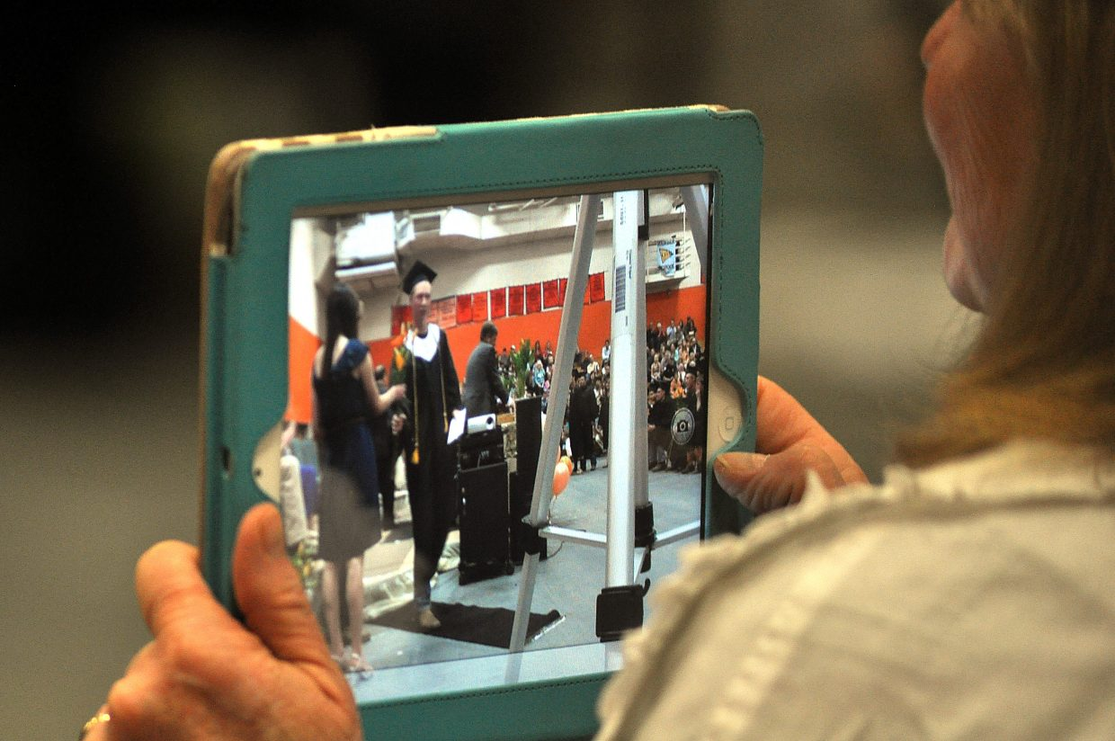 A woman takes pictures of the graduation ceremony on an iPad.