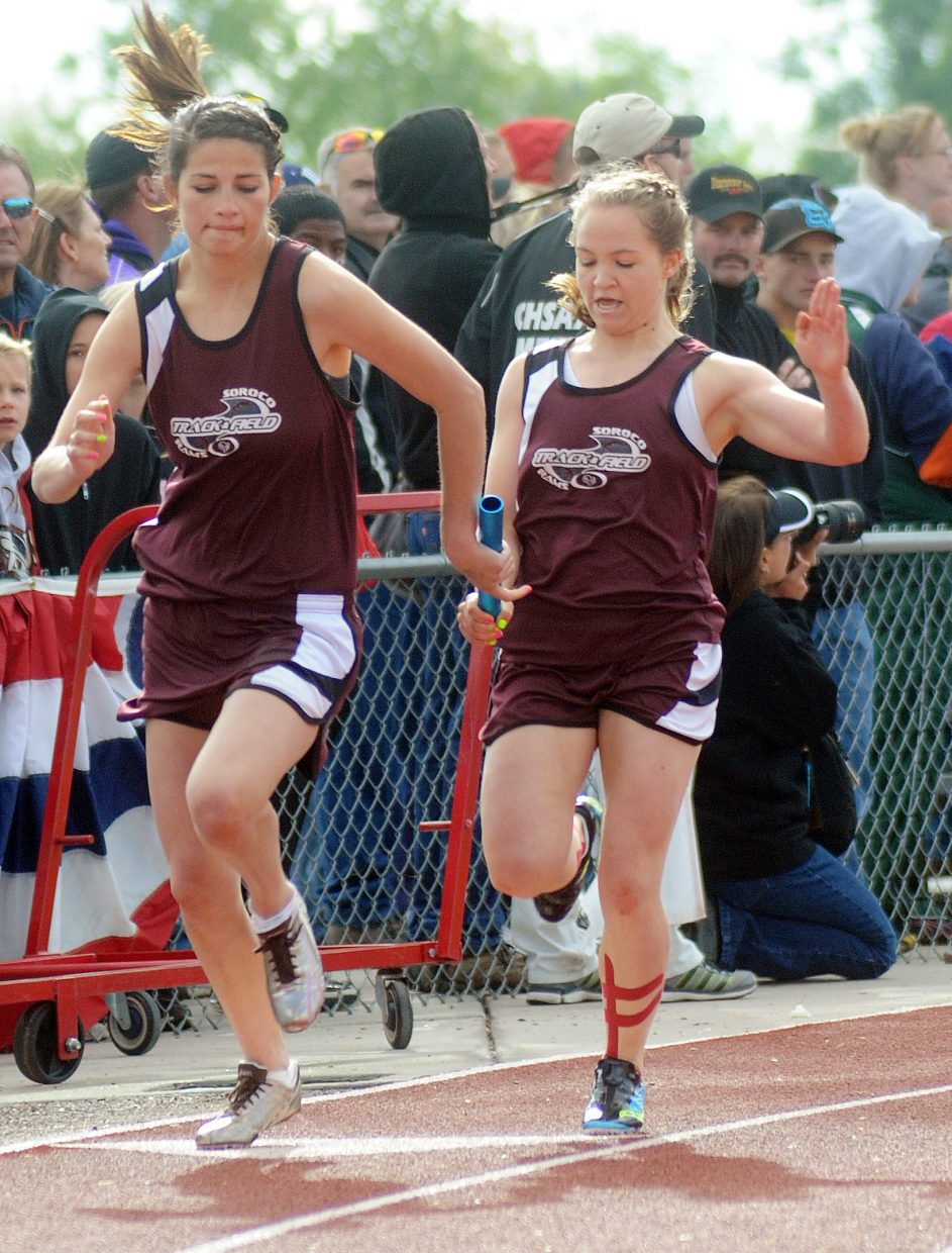Lauryn Bruggink hands the baton off to Ceanna Rossi in the girls 800-meter relay Friday at the state track meet in Lakewood.